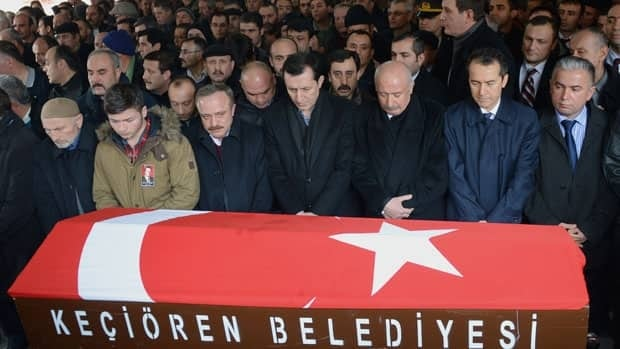 People gather on Saturday behind a Turkish flag-covered coffin of Mustafa Akarsu, an embassy security guard killed when a suicide bomber struck the American Embassy in the Turkish capital on Friday.
