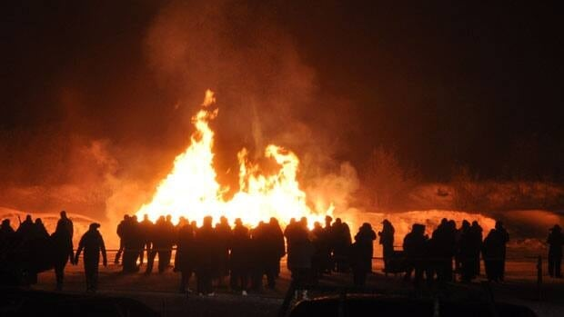 People gathered around a large bonfire in the community Saturday night.