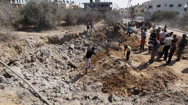 Palestinians inspect the damage following an Israeli air strike in Al-Zawaida in the central Gaza Strip on Monday.