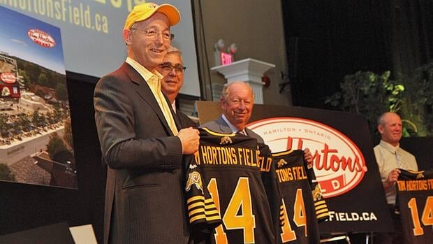 Hamilton Tiger-Cats owner Bob Young, left, holds up a special Ticats jersey after announcing the team's new stadium, which will open in 2014, will be named Tim Hortons Field.
