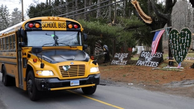 A school bus in Newton, Conn. passes a memorial near the Sandy Hook Elementary School where a mass shooting last December killed 20 children and six school employees.