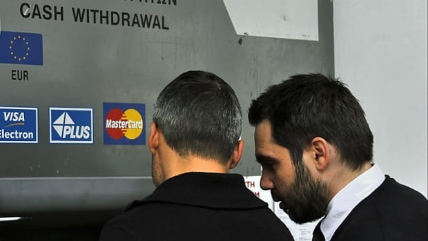 Cypriots try to withdraw money from bank machines in the midst of the country's unfolding financial crisis.
