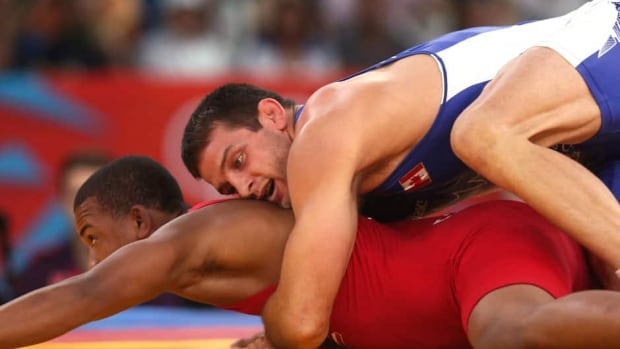 Canada's Matthew Judah Gentry,right, wrestles Puerto Rico's Francisco Daniel Soler Tanco in Men's 74kg Freestyle repechage in London 2012 Olympic Games.
