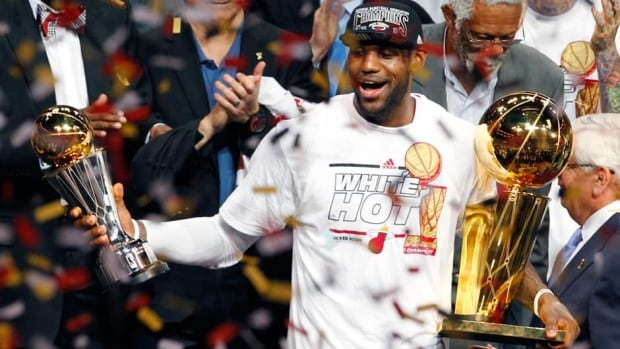 Miami Heat's LeBron James holds the Larry O'Brien Trophy, right, and the Bill Russell MVP trophy after the Heat defeated the San Antonio Spurs to win Game 7 of the NBA Finals on Friday.