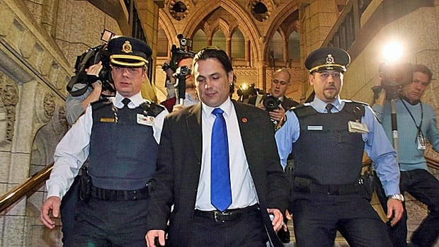 Senator Patrick Brazeau is escorted out of the Parliament buildings Tuesday after he was suspended from duties by the Senate in wake of the criminal charges he is facing.