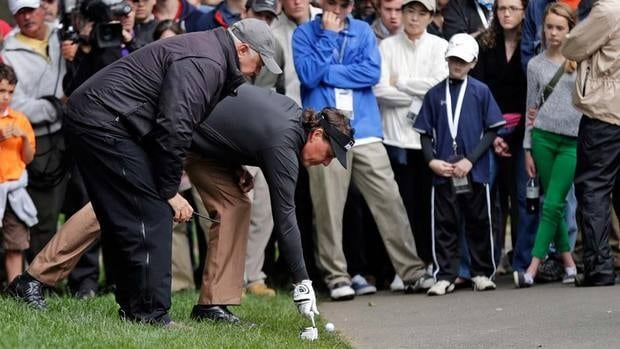 Phil Mickelson gets a ruling from an official after his second shot on the 15th hole during the third round of the Wells Fargo Championship golf tournament at Quail Hollow Club in Charlotte on Saturday. Mickelson is tied for the top.