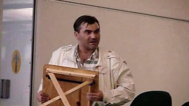 Robert Dziekanski holds a small table at the Vancouver airport before he was stunned with a Taser by police in this image from video. The B.C. Coroner's Service says the death of the Polish immigrant six years ago was a homicide.