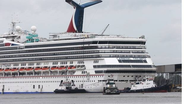 Tugboats manoeuvre around the Carnival cruise ship Triumph as it rests against a dock on the east side of the Mobile River in Alabama after becoming dislodged from its mooring at BAE Shipyard during high winds Wednesday.