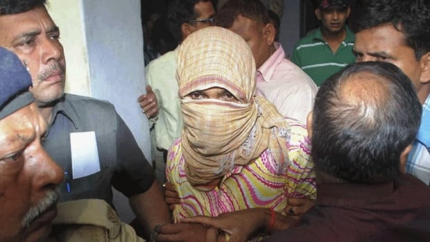Police officers escort a man, accused of raping and torturing a five-year-old girl, at a court in Muzaffarpur in the eastern Indian state of Bihar.