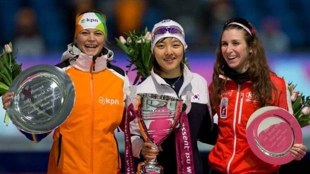 Mariska Huisman of The Netherlands, left and second place, Bo-Reum Kim of Korea, centre and first place, and Ivanie Blondin of Canada, right and third place, celebrate on the podium of the women's mass start of the World Cup speed skating at Thialf ice rink in Heerenveen, northern Netherlands, Sunday.