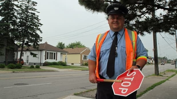 One of the city's approximately 250 crossing guards, Cass Heller mans the intersection at East 5th and Fennell on the Hamilton Mountain, in front of Sts. Peter and Paul Catholic Elementary School.