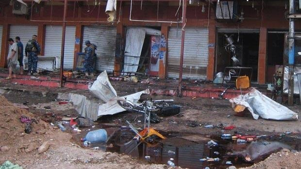 Security forces inspect the scene of a suicide bomb attack at a coffee shop in Kirkuk.