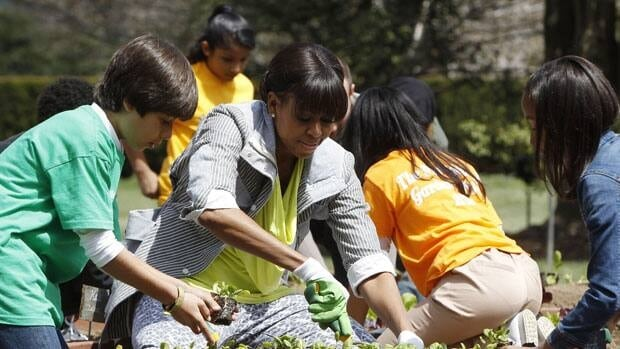 U.S. first lady Michelle Obama and school children plant spinach at the White House kitchen garden on the south lawn on Thursday.