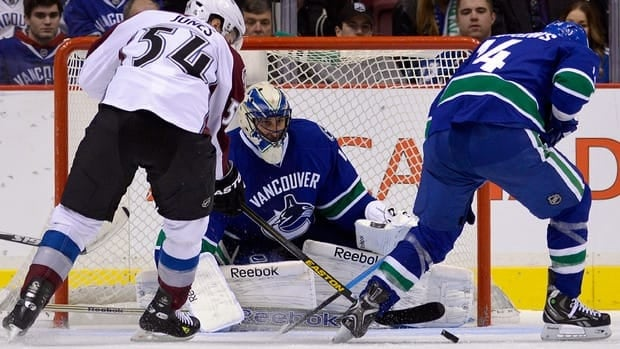 Vancouver Canucks goaltender Roberto Luongo, centre, keeps an eye on the loose puck after making a save as David Jones of the Colorado Avalanche, left, and Alexandre Burrows, right, battle for possession on Wednesday evening in Vancouver.