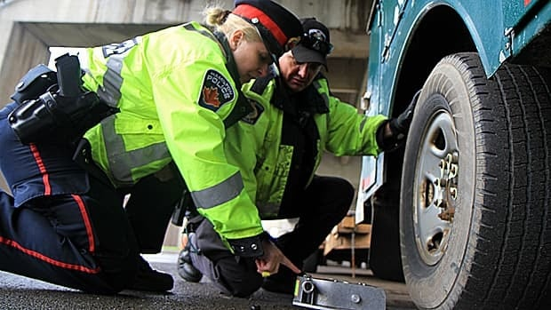 Const. Joanne Serkyn and Const. Pat Martin inspect a truck during a commercial vehicle inspection stop in Hamilton this week. The officers found a high number of trucks with faulty brakes, poor tires and wheels in danger of coming unfastened.