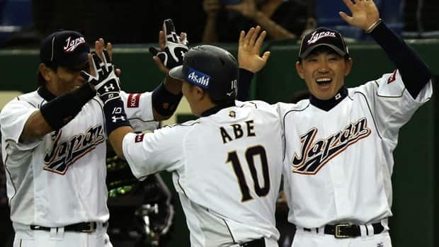 Japan's designated hitter Shinnosuke Abe celebrates with teammates Seiichi Uchikawa, right, and Atsunori Inaba after hitting a three-run homer in Tuesday's game at Tokyou Dome.