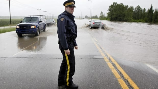 RCMP Cst. Ian Gillard driects traffic through a flooded intersection near Bragg Creek, Alta. The community, just outside of Calgary city limits, was one of the first to be hit by intense flooding in southern Alberta.
