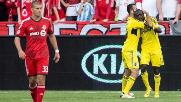 Columbus Crew's Dominic Oduro, right, celebrates with Justin Meram after scoring as Toronto FC's Ryan Richter, left, looks on during the first half Saturday.