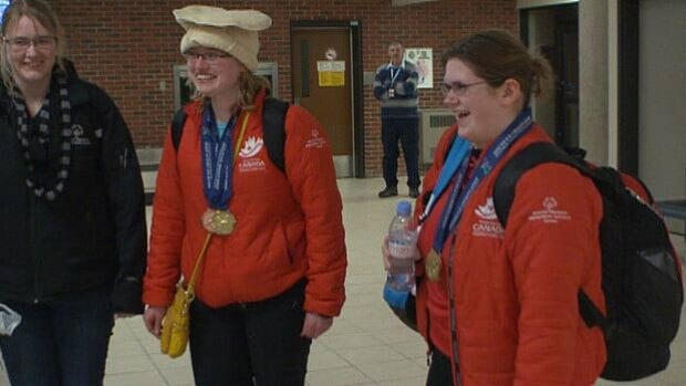 Alyssa Chapman of Murray Habour and Ellen McNearney of Montague arrived at Charlottetown Airport with their medals in the early hours of Thursday morning.