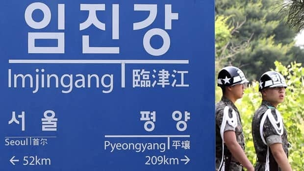 South Korean army soldiers walk by a signboard near the border village of the Panmunjom in Paju, South Korea, Friday. North Korea on Friday proposed working-level talks with South Korea to be held in a border city on Sunday.