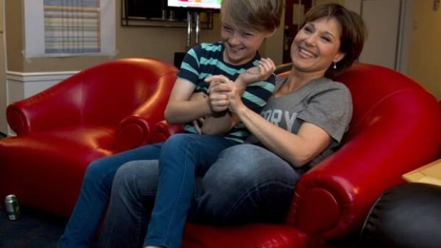 BC Liberal leader Christy Clark and her son Hamish Marrisen-Clark, 11, share a laugh as they watch the results come in on TV of the 2013 British Columbia provincial election.