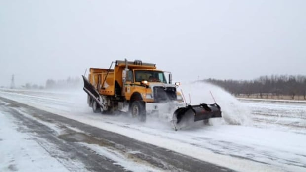 A snow plow drives along the highway clearing the road of ice and snow. (Katie Nicholson/CBC)