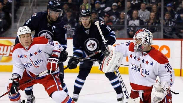 Winnipeg Jets forwards Andrew Ladd (16) and Bryan Little (18) hope to beat Washington Capitals' Steve Oleksy (61) to the rebound as Capitals goalie Braden Holtby (70) stops the shot during the second period in Winnipeg on Friday.