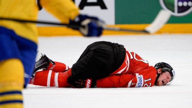 Canada's Eric Staal lies injured on the ice after a hit by Sweden's Alexander Edler during Thursday's quarter-final game in Stockholm.