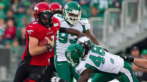 Calgary Stampeders quarterback Drew Tate runs the ball past Saskatchewan Roughriders linebacker Renauld Williams in the first quarter of a pre-season game last month.
