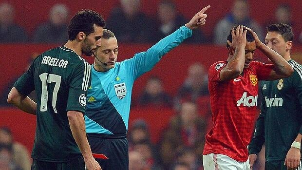 Manchester United's midfielder Nani holds his head as Turkish referee Cuneyt Cakir sends him off after a challenge against Real Madrid's defender Alvaro Arbeloa in Tuesday's match.