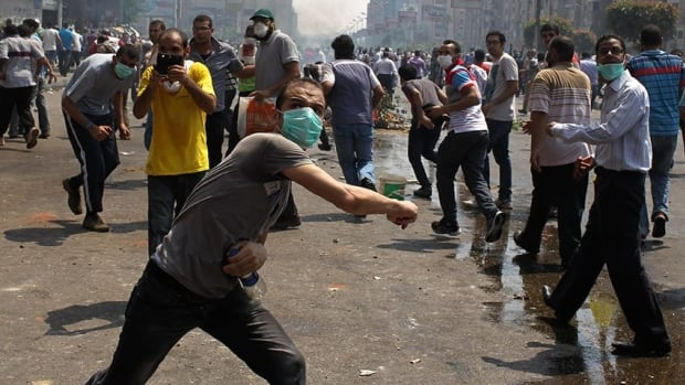 Members of the Muslim Brotherhood and supporters of ousted Egyptian President Mohamed Mursi clash with police near Rabaa Adawiya square in Cairo on Aug. 14, 2013. Egypt's interim president has declared a month-long state of emergency to combat worsening violence after riot police moved to clear two encampments of supporters of ousted Islamist president Mohammed Morsi.