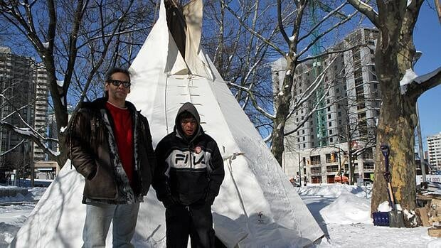 He Carries the Strength of 10 Buffalo (left) and Mark Berguist outside a teepee that's been erected outside Hamilton City Hall. Strength started a four-day hunger strike in which he will only consume liquids early Friday.