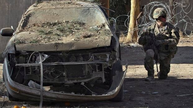 A U.S. soldier investigates the scene after two suicide attacks, south of Kabul last month. The American-led coalition acknowledged an error in reporting a 7 per cent drop in Taliban attacks.