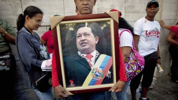 A supporter of Venezuela's President Hugo Chavez holds a photograph of Chavez outside the National Assembly in Caracas, Venezuela. Just one day remains until Chavez's scheduled inauguration on Jan. 10, but lawmakers have voted to postpone the ceremony.