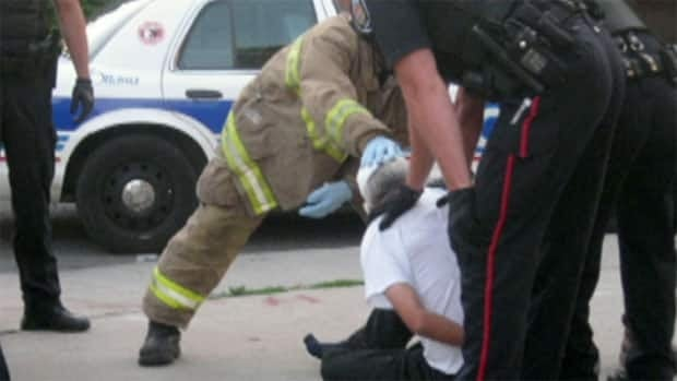 This is a cropped version of a photo taken by Tash Doucette as police deal with Hugh Styres, a homeless man who was sleeping on an Osgoode Street sidewalk.