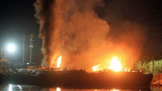 Fire burns aboard two fuel barges along the Mobile River after explosions sent three workers to the hospital Wednesday night.