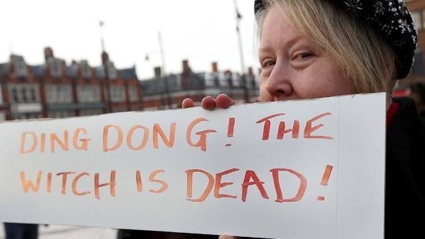 A woman poses behind a sign displaying the message Ding Dong! The Witch is Dead! as she celebrates the death of former British prime minister Margaret Thatcher in Brixton, England, on April 8.