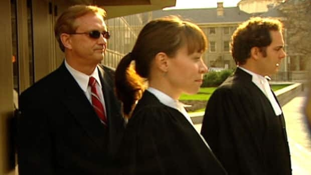 Richard Dow, left, leaves the Winnipeg courthouse with his lawyers on April 30, after a jury found him not guilty of sexually assaulting a female client of Ricoco International, a modelling agency he ran as a side business.