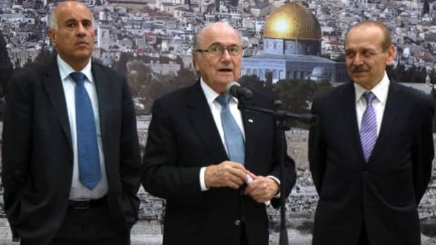 FIFA president Sepp Blatter, middle, talks to reporters flanked by PFA president Jibril Rajoub and politician Yasser Abed Rabbo.