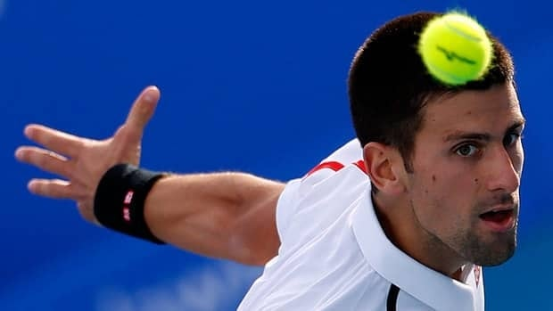 Novak Djokovic returns the ball to David Ferrer during an exhibition tournament Friday in Abu Dhabi.