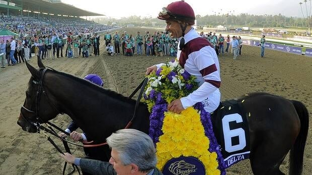 Jockey Mike Smith riding Royal Delta looks skyward while celebrating victory in the Breeders' Cup Ladies' Classic race at Santa Anita racetrack in Arcadia, Calif. on Friday.