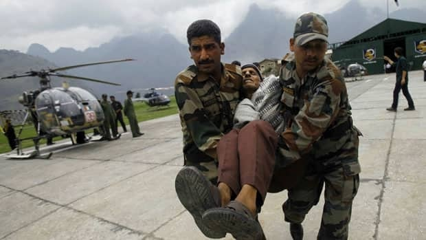 An injured Indian pilgrim cries in pain as Indian army soldiers carry him after he was rescued from the higher reaches of mountains at a makeshift helipad at Joshimath, in northern Indian state of Uttarakhand.