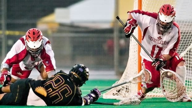 Canada goaltender Chris Sanderson, right, makes a save on Iroquois Nation's Brett Bucktooth's shot as he's checked by Jim Moss during action at the World Lacrosse Championships in London, Ont., on July 20, 2006. Sanderson, a champion on and off the field, died Thursday. He was 38.