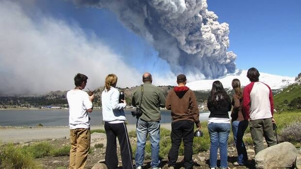 Local residents watch a column of smoke and ash rise from the Copahue volcano, located on the Chilean-Argentine border, from Caviahue in the Argentina patagonian province of Neuquen on December 22, 2012. Volcanic activity has prompted Chilean authorities to  declare a red alert on Monday.