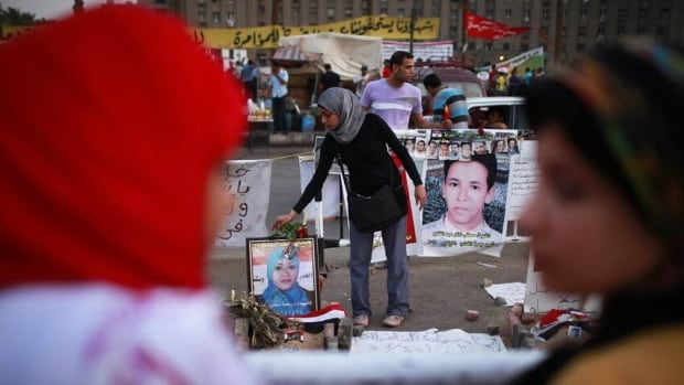 A protester in Tahrir Square places a flower on a picture of a woman who was killed in Egypt's revolution. The square was the site of an attack on women who were protesting sexual harassment Friday.