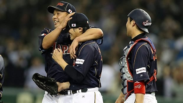 Japan's captain Shinnosuke Abe holds closer Toshiya Sugiuchi after the win at Tokyo Dome on Friday.
