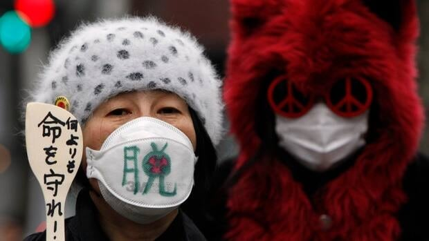 A protester at an anti-nuclear march in Toky is shown. Japan's energy policy remains to phase out nuclear power, though it would take time, the government said Wednesday.