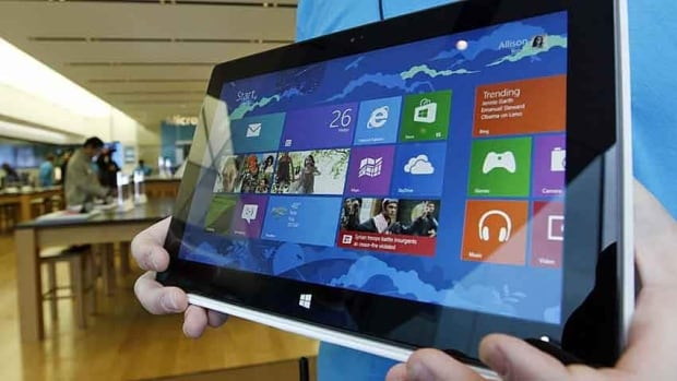 A Microsoft store product adviser displays the new Surface tablet computer as customers enter the store Friday in Seattle. Friday was the first day of sales for the new Windows 8 operating system and the company's new tablet computer.
