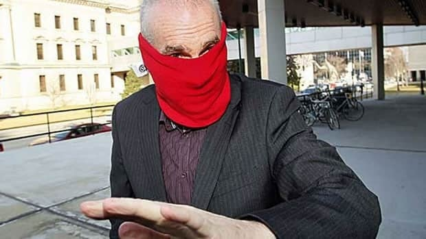 Graham James hides his face as he pushes past photographers in Winnipeg on Tuesday.