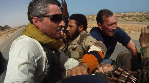 Reuters photographer Finbarr O'Reilly is shown in Libya. The Peabody Award-winning documentary Under Fire: Journalists in Combat looks at the dangers and stresses reporters face in conflict zones.